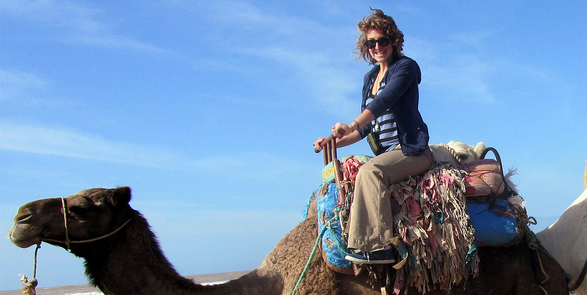 woman in sunglasses in the desert sitting atop a camel