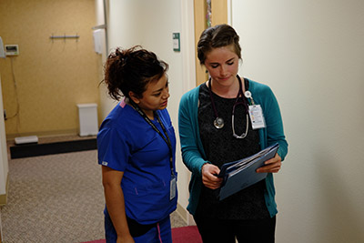 Medical assistants confer over charts