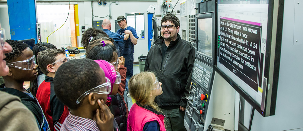 Machinist Dan Porter (right) demonstrates an Okuma router to a group of visiting students during a school tour at the Seattle facility