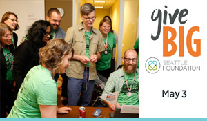 staff wearing green shirts gathered at desk for givebig small banner