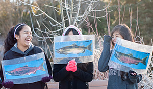 Students at an environmental class show off pictures of salmon species
