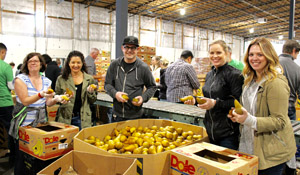 Volunteers pack fruit at Food Lifeline's distribution center.