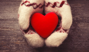 Hands in mittens hold a red heart