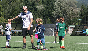 Jordan Morris interacts with kids at his soccer camp