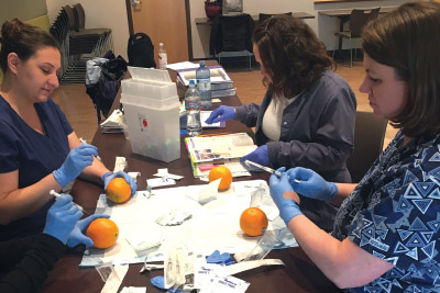 Medical assistants practice using syringes on oranges