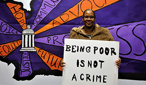 "An activist for Statewide Poverty Action Network holds a sign that says ""Being Poor is Not a Crime"""