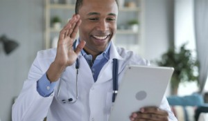 Teledoctor smiling while holding a tablet and waving at a patient on a video conference call