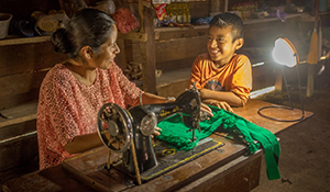 Impact Investing Opportunities image with woman at sewing machine while child looks on