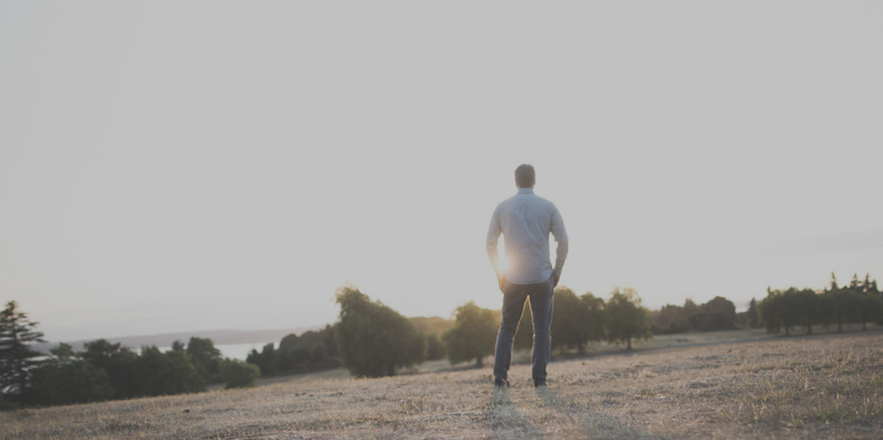 man standing in field silhouetted with gray overlay